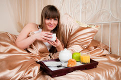 Woman Eating Breakfast And Drinking Coffee In Bed. Royalty Free Stock Images