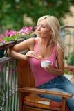 Woman eating breakfast on balcony Stock Image