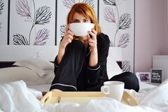 Woman eating breakfast in bed Stock Photos