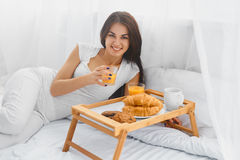 Woman eating breakfast in bed Stock Image