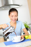 Woman eating breakfast and drinking coffee Stock Images
