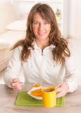 Woman eating breakfast at home Stock Photography