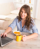 Woman eating breakfast at home Stock Image
