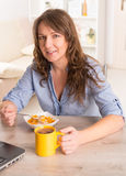 Woman eating breakfast at home Stock Photo