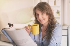 Woman eating breakfast at home stock images