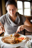 Woman eating breakfast Stock Photography