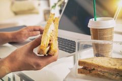 Woman eating a breakfast sandwich while working with a laptop stock image