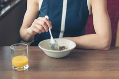 Woman eating breakfast by window in diner Stock Photo