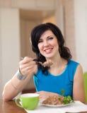 Woman eating buckwheat porridge Stock Images
