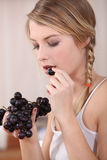 Woman eating bunch of grapes Stock Photography