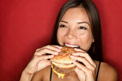 Woman eating burger. Burger woman smiling eating junk food burger happy. Pretty mixed race caucasian asian girl on red background royalty free stock image