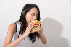 Woman eating burger over white background royalty free stock image