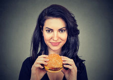 Woman eating burger smiling. Beautiful female model Royalty Free Stock Images