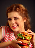 Woman eating burger and winks. Happy student eat sandwich lunch. Stock Photo