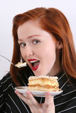 Woman eating cake. A portrait of a young redheaded woman about to eat and enjoy a piece of frosted layer cake that she is holding with a fork Royalty Free Stock Photography