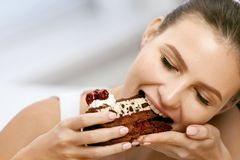 Woman Eating Cake. Beautiful Female Eating Dessert. Portrait Of Happy Smiling Young Woman Biting Piece Of Chocolate Cake. Sweets And Food Concept. High Quality royalty free stock images