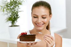 Woman Eating Cake. Beautiful Female Eating Dessert. Portrait Of Happy Smiling Young Woman Biting Piece Of Chocolate Cake. Sweets And Food Concept. High Quality stock photo