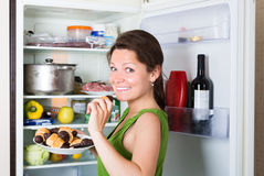 Woman eating cake from fridge Stock Photography