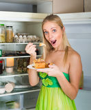Woman eating cake from fridge. Young smiling woman eating cake from fridge at home royalty free stock image