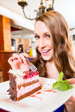 Woman eating cake at pastry shop cafe. Young woman eating fruit cake at cafe or bakery Royalty Free Stock Images