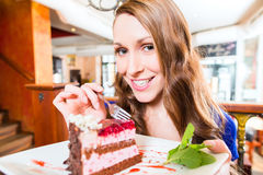 Woman eating cake at pastry shop cafe. Young woman eating fruit cake at cafe or bakery Stock Photography