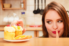 Woman eating cake showing quiet sign. Gluttony. Stock Photo