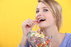 Woman eating candy Stock Photos
