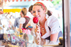 Woman eating candy apple at Oktoberfest or Dult Stock Photo
