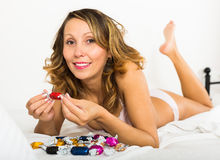 Woman eating candy in bed Stock Image