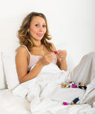 Woman eating candy in bed Stock Images