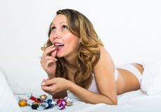 Woman eating candy in bed Royalty Free Stock Photo