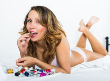 Woman eating candy in bed Royalty Free Stock Photography