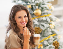 Woman eating candy with latte macchiato near christmas tree Stock Photo