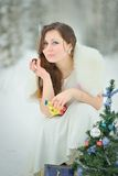 Woman eating a candy in winter forest Stock Image