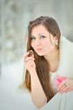 Woman eating a candy in winter forest Stock Photos