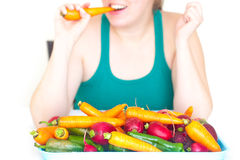 Woman eating a carrot and a heap of vegetables. Young woman eating a carrot and a heap of vegetables Stock Photo