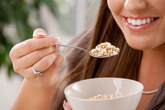 Woman eating cereal. Closeup of partially visible young woman eating breakfast cereal. Selective focus on spoon Stock Photo