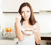 Woman eating cereal in  kitchen. Royalty Free Stock Image
