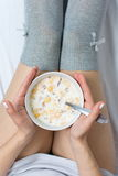 Woman eating cereals in bed. Top view Stock Images