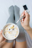 Woman eating cereals in bed. Top view Stock Photos