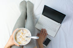 Woman eating cereals in bed. Top view Royalty Free Stock Photography
