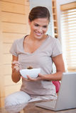 Woman eating cereals while looking at her laptop. Young woman eating cereals while looking at her laptop Stock Photography