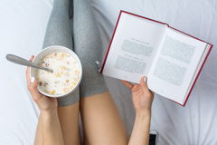Woman eating cereals and reading in bed. Top view Royalty Free Stock Image