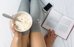 Woman eating cereals and reading in bed Royalty Free Stock Photo