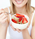Woman eating cereals with strawberries. Close-up of a caucasian woman eating cereals with strawberries against a white background Stock Image