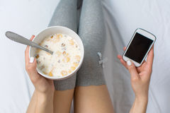 Woman eating cereals and texting in bed Royalty Free Stock Image