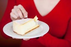 Woman eating cheese cake Stock Photos