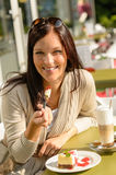 Woman eating cheesecake at cafe bar happy Royalty Free Stock Photos