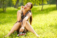 Woman Eating cherries. A young woman eating a handful of cherries outdoors Stock Photography