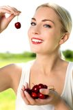 Woman eating cherries. Young woman eating cherries, smiling Royalty Free Stock Images